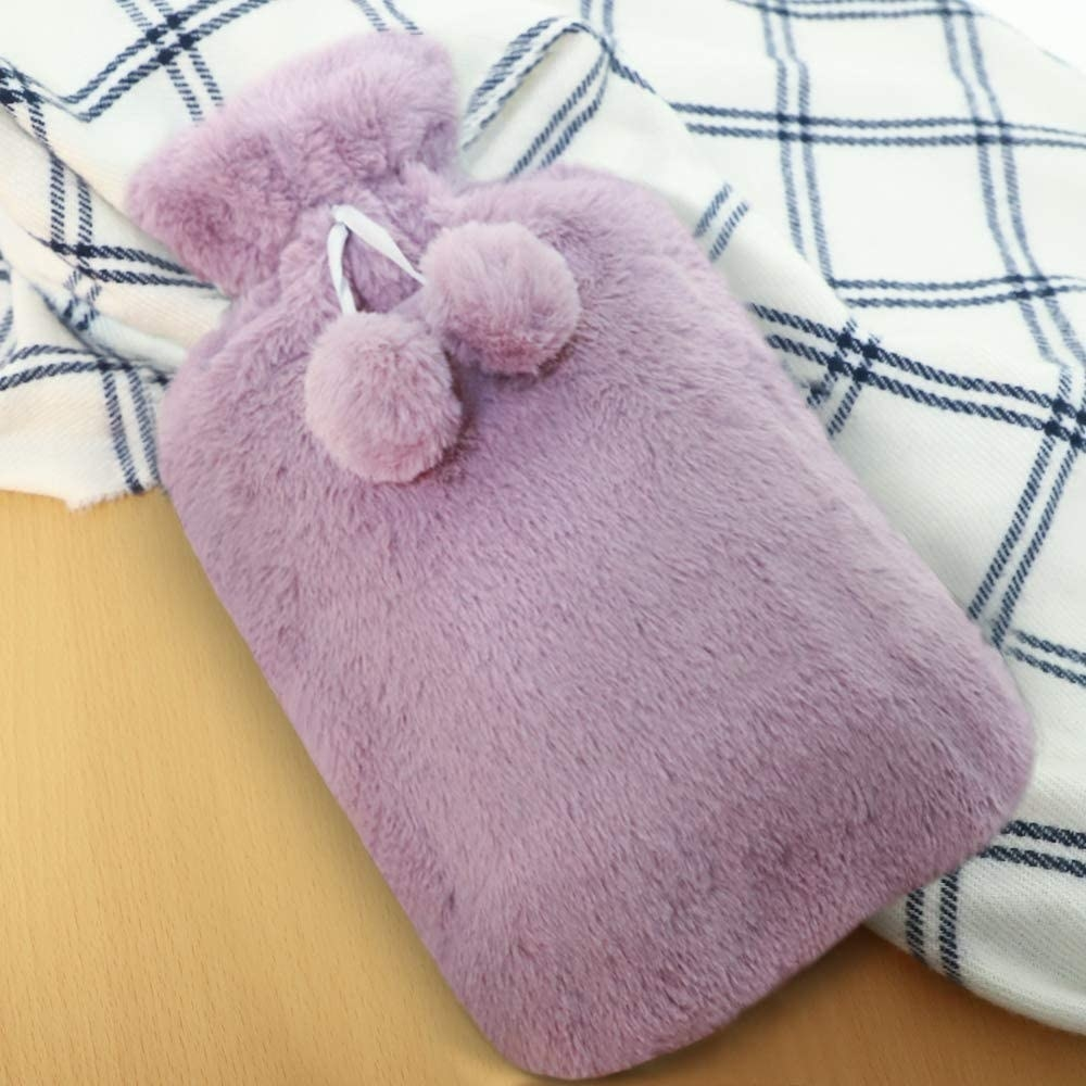 A flatlay of the fuzzy hot water bottle on a flannel blanket