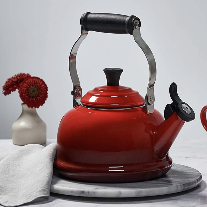 A red Le Creuset tea kettle with a large metal handle