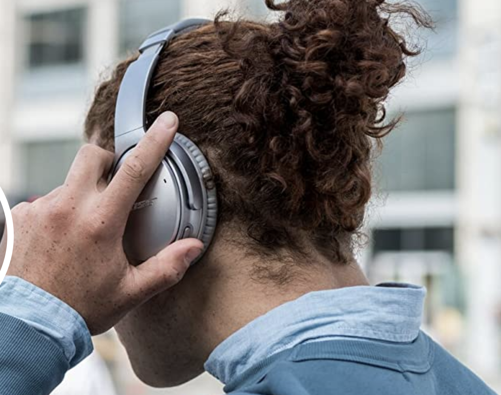 A model wearing a pair of gray over the ear wireless headphones