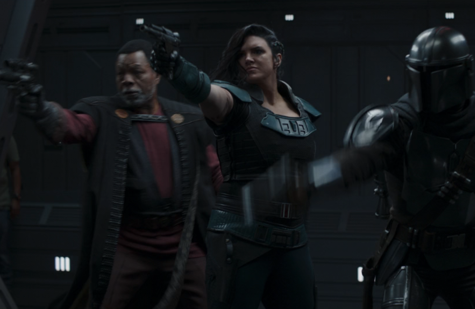 Greef, Cara, and the Mandalorian firing blasters in a corridor with a crew member in jeans and a T-shirt barely visible on the left side of the screen