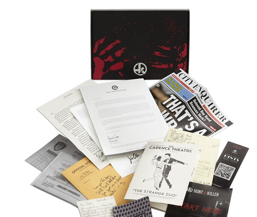 A Hunt A Killer box with newspaper clippings, police documents, letters, and other paperwork