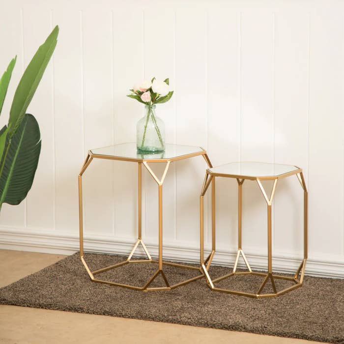 the two hexagon shaped tables with glass tops and gold legs and edges