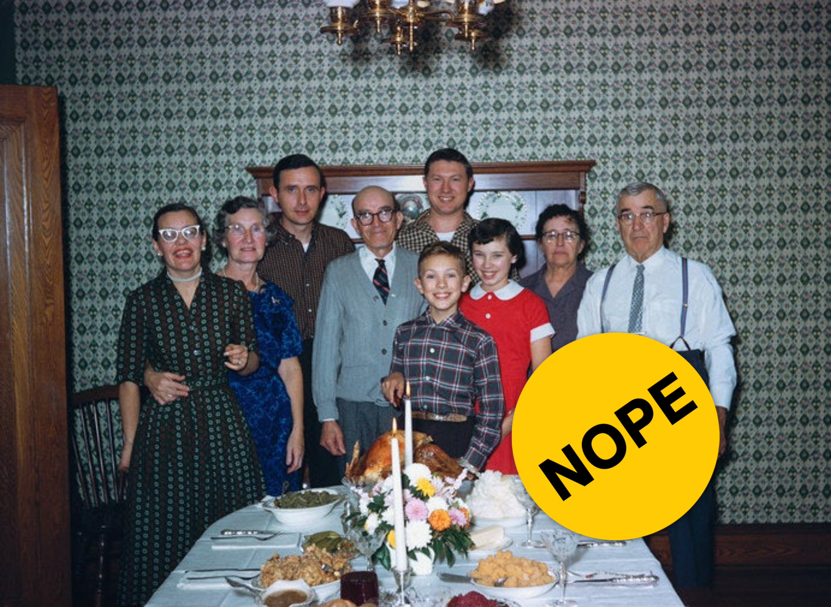 """Multi-generational family standing behind a thanksgiving table with """"Nope"""" label photoshopped on top."""