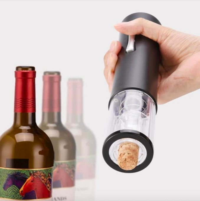 A person holding up the electric wine opener with a cork attached at the bottom