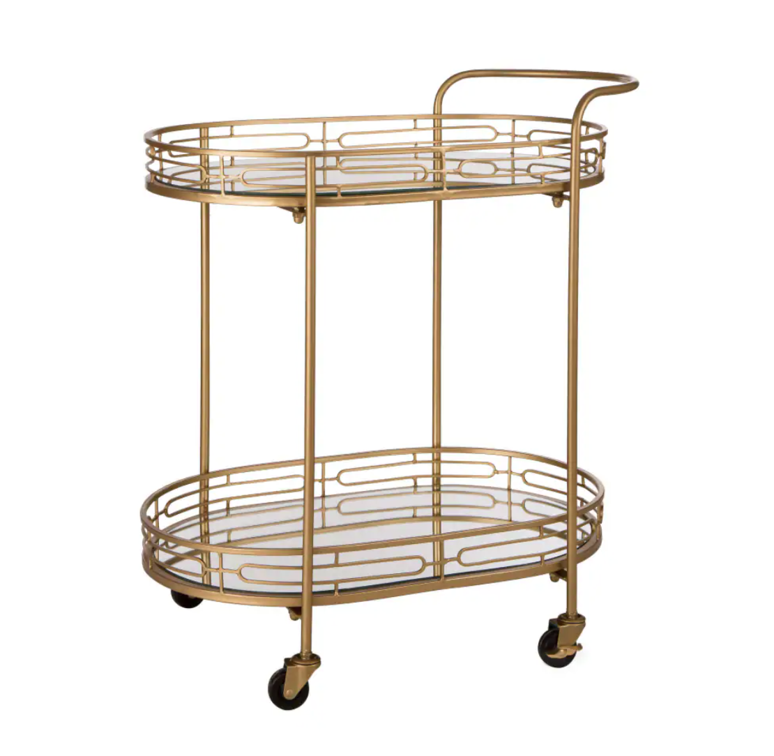 a gold oval bar cart on wheels