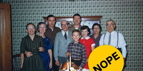 Multi-generational family standing behind a thanksgiving table with