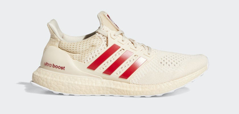Cream-colored shoes with red adidas stripes