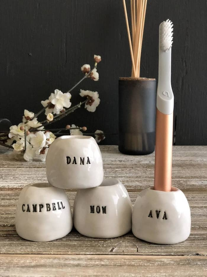 Four toothbrush holders with names on them