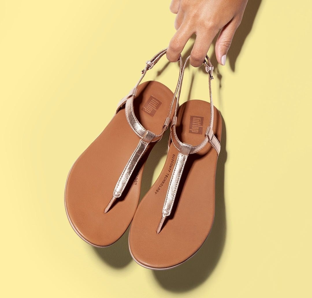 Hands holding a pair of strappy metallic rose gold sandals with a brown leather sole