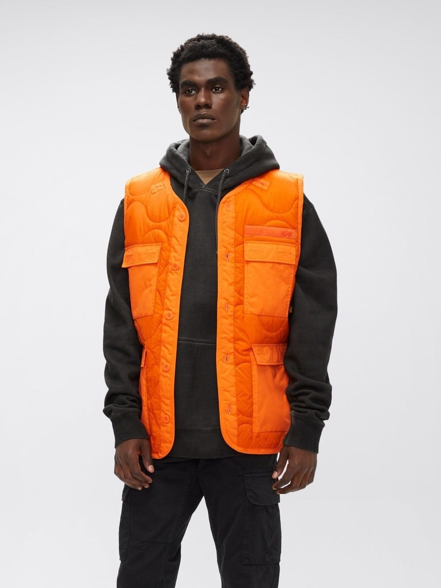 a model wears the als utility vest