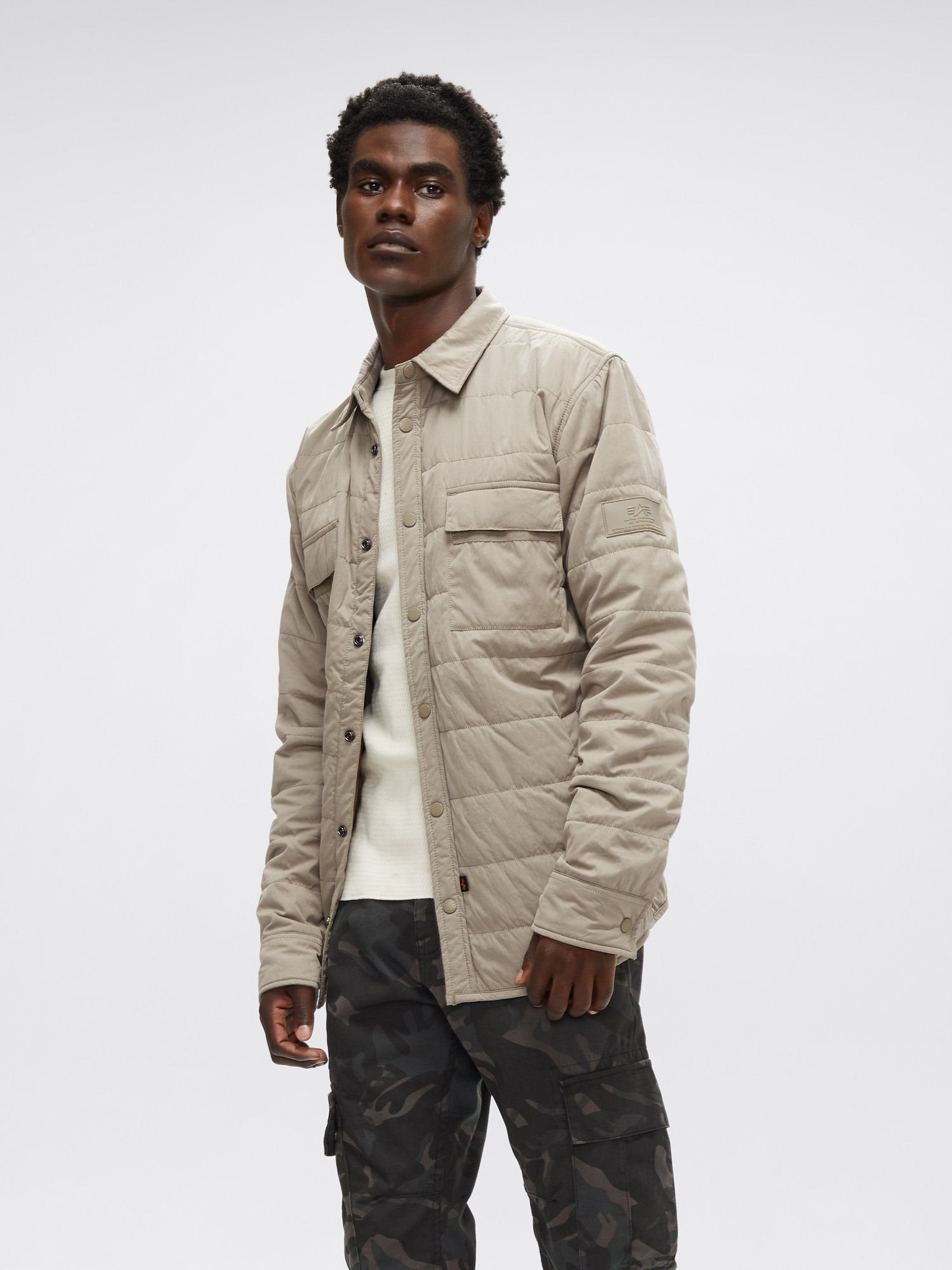 a model wears the quilted shirt utility jacket in dark khaki