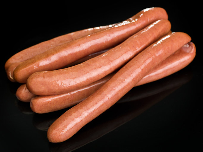 bunch of frankfurter sausages on black background