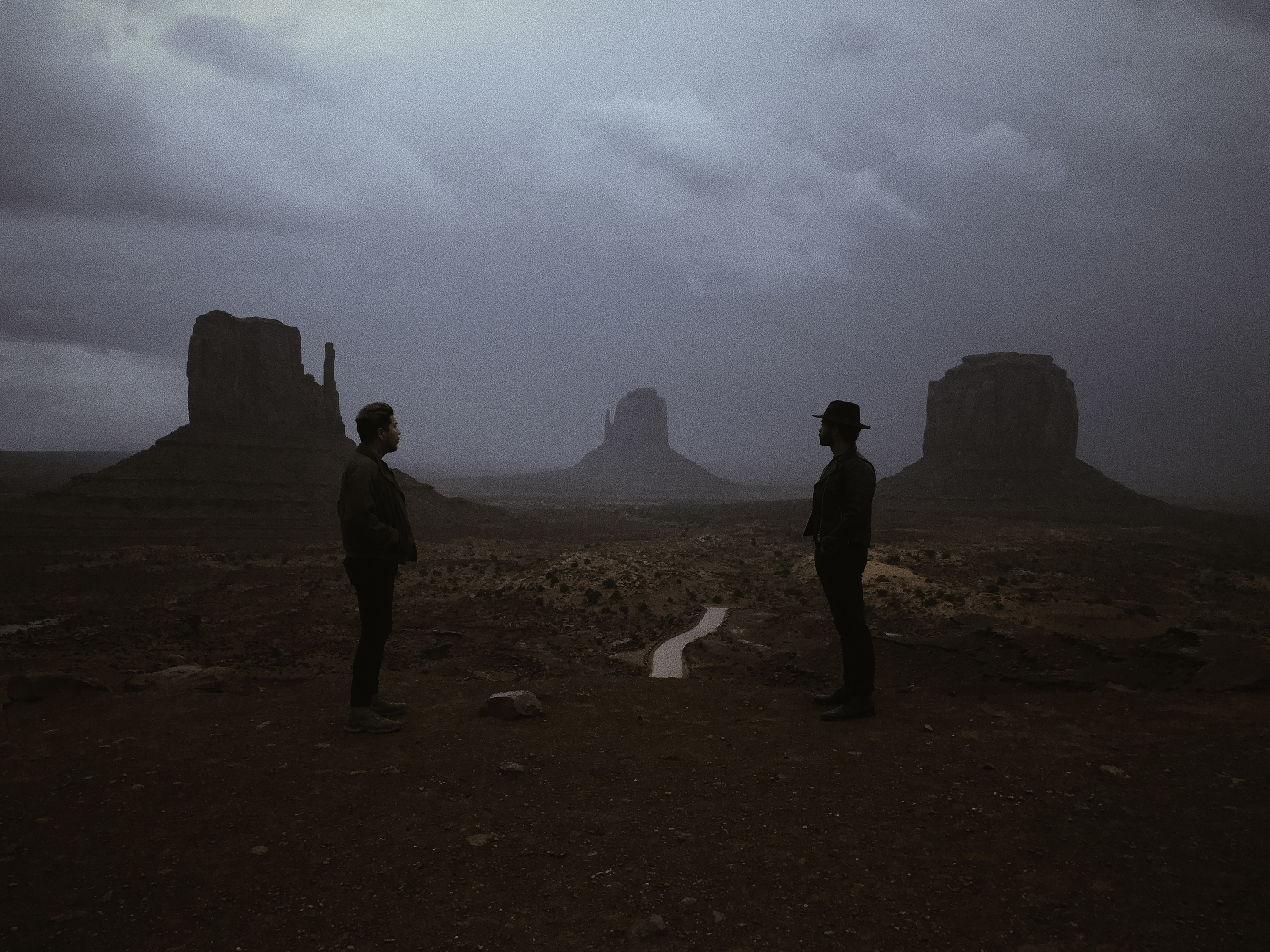 Two men, one in a hat, staring out over a landscape with buttes and a road on a cloudy day.