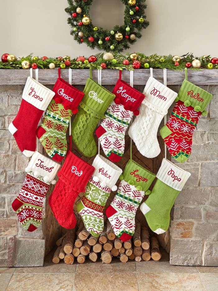 The custom stockings in an assortment of colors hanging from a fire place