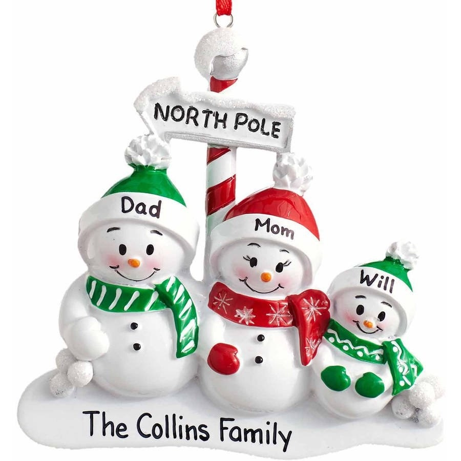 The snowmen ornament with two parents and a child wearing red and green scarves