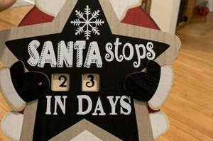 Santa holding a sign that says,