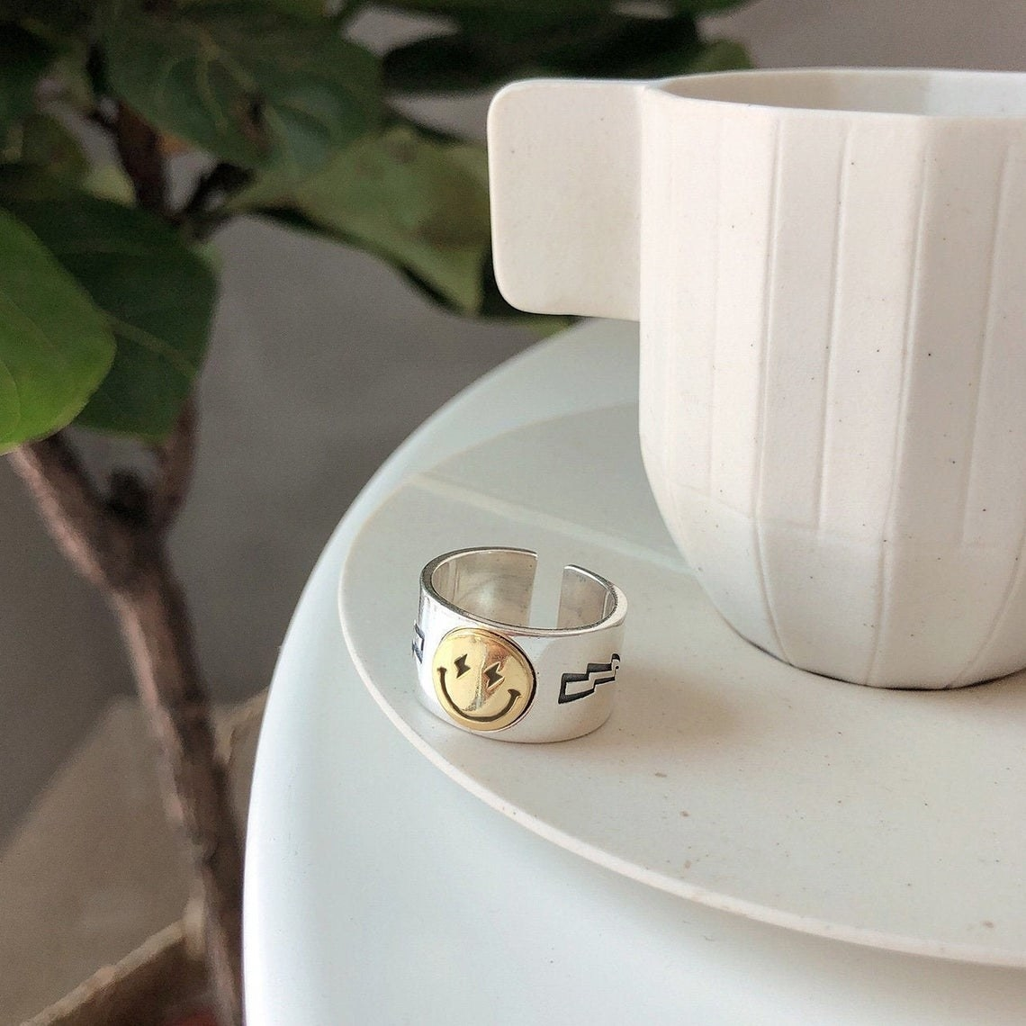 The smiley face ring next to a fiddle leaf fig tree and mug