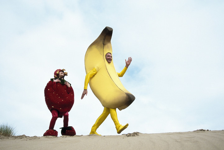 Man dressed as a banana and woman dressed as a strawberry on a beach