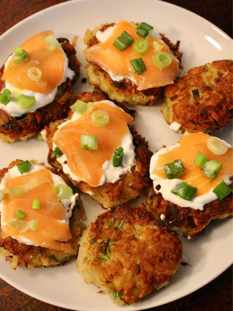 A plate of potato latkes, some of which are topped with crème fraîche and smoked salmon.