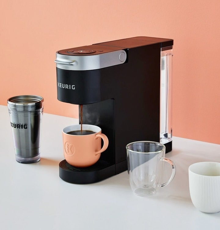 The Keurig slim coffee maker on a counter next to four different coffee mugs