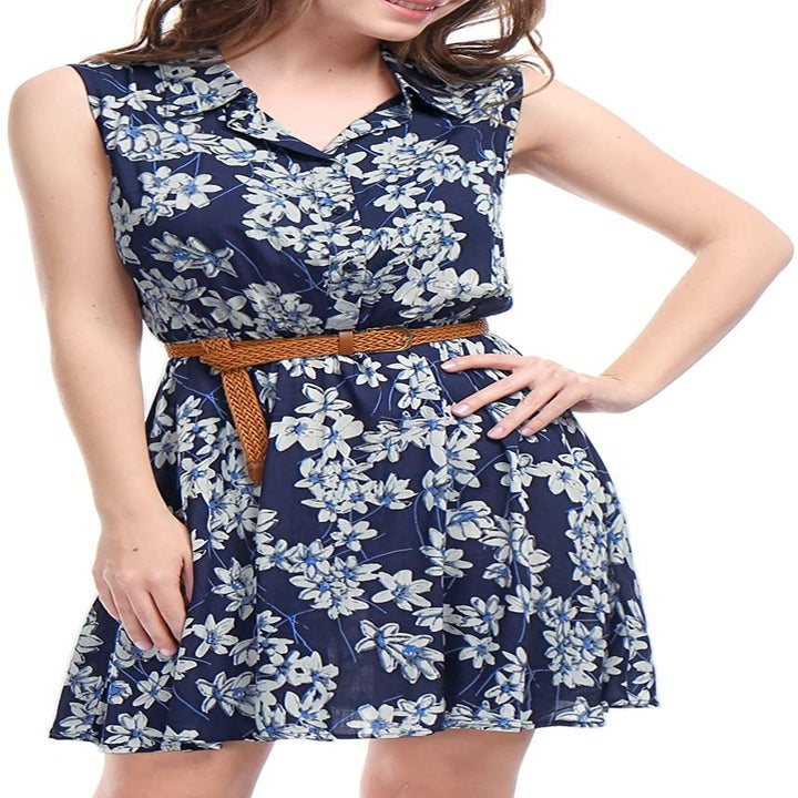 A model in the sleeveless collared dress with a brown braided belt in blue floral print