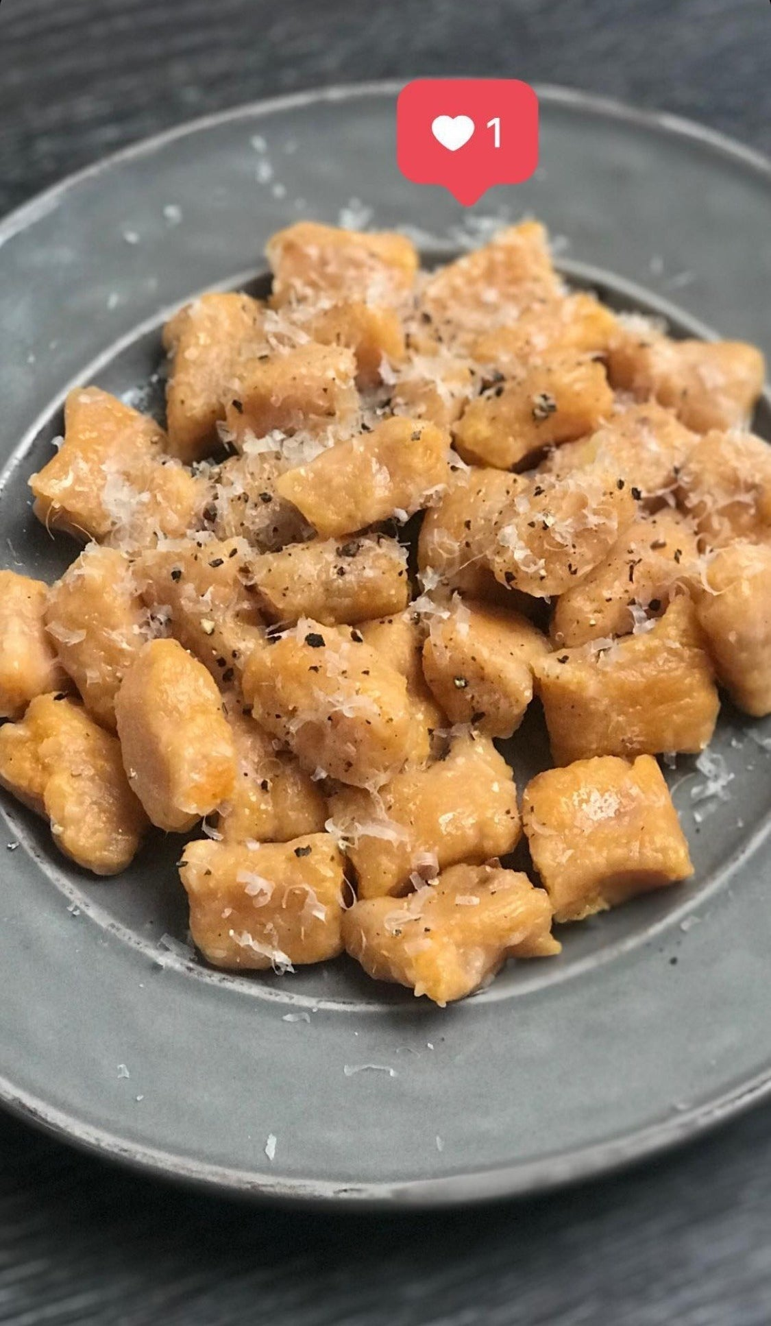 A plate of brown butter sweet potato gnocchi with Parmesan.