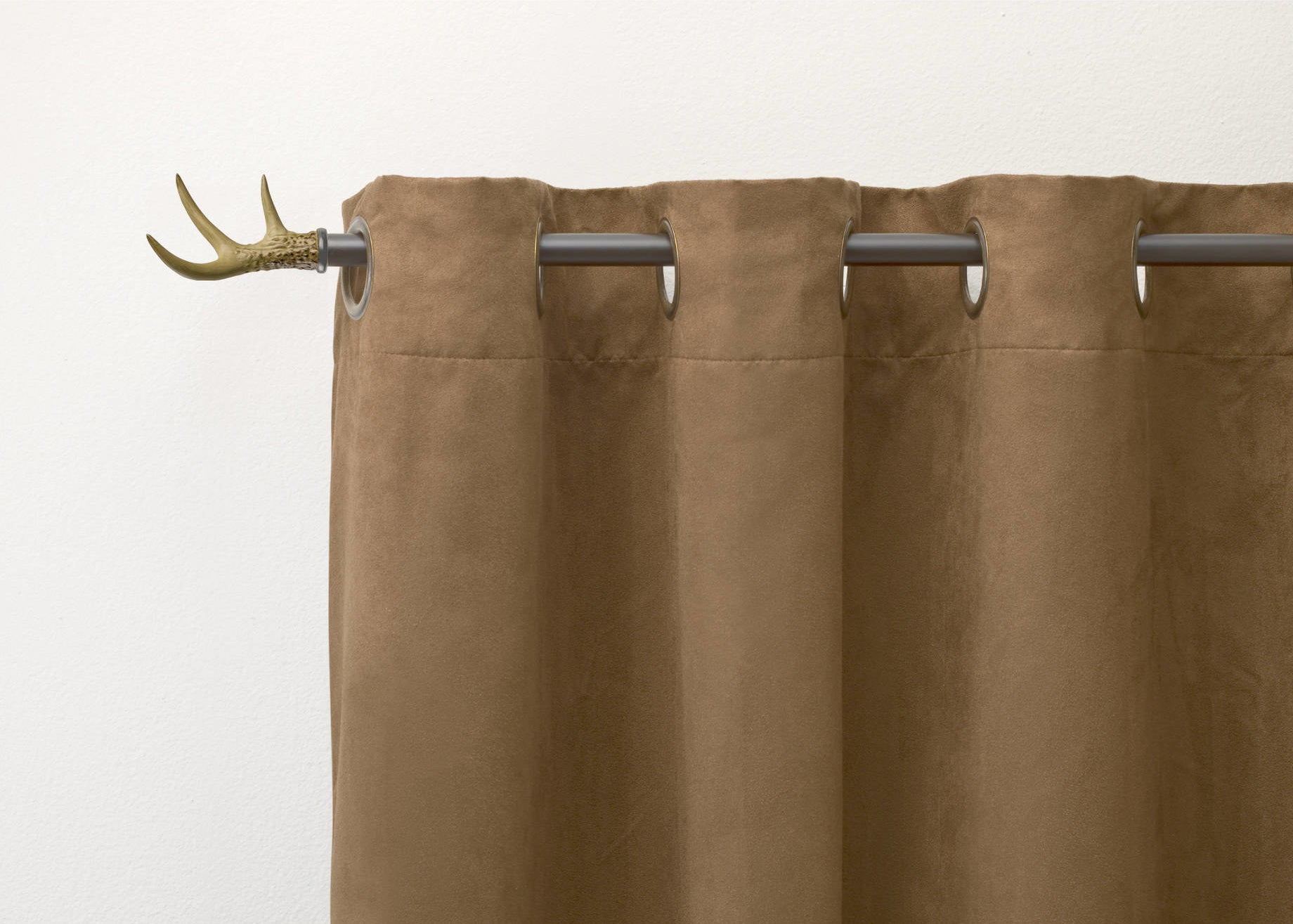 The curtain rod with a golden finish and brown curtains hanging from it