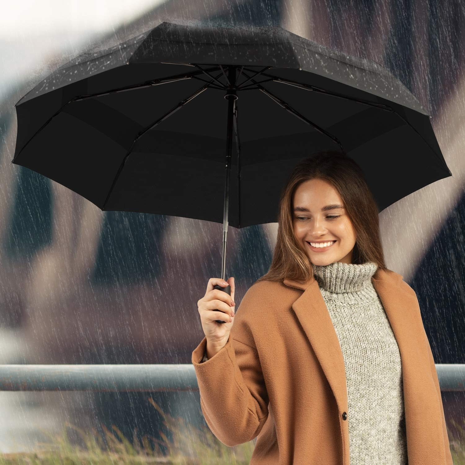 A smiling person holding the umbrella up during a windy rainstorm