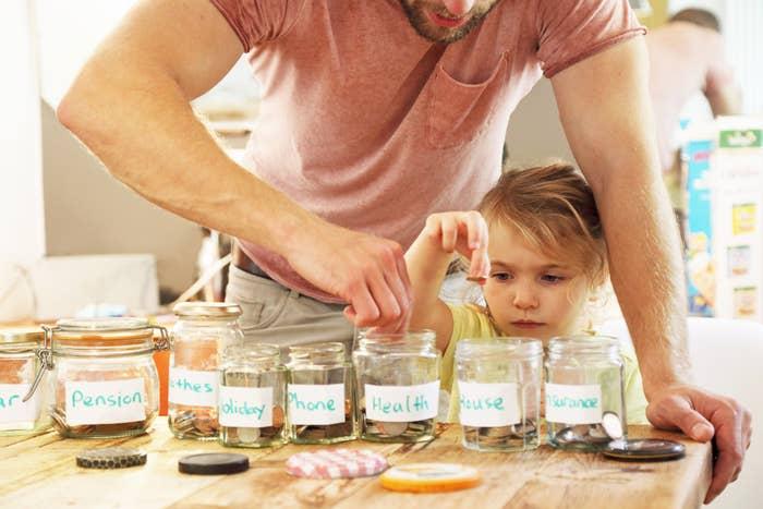 dad with kid putting money in savings jar