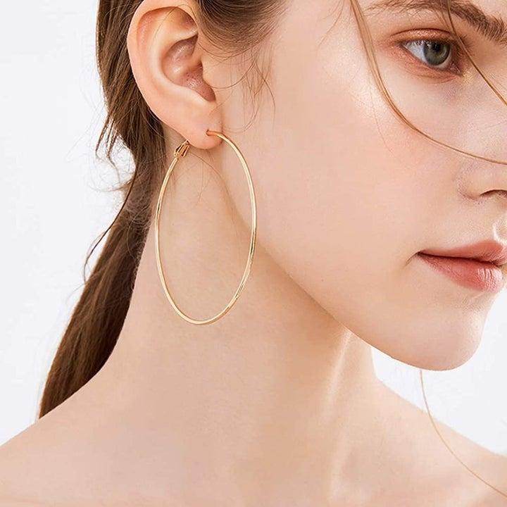 Model wearing gold hoop earring on right ear