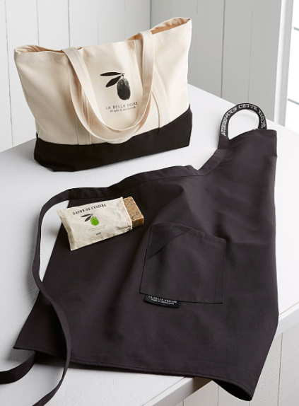The three piece chef's set consisting of a tote, an apron, and solid soap on a plain kitchen counter