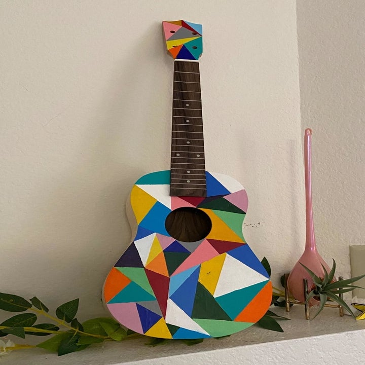 A reviewer's photo of their ukulele which is painted with colorful geometric triangles