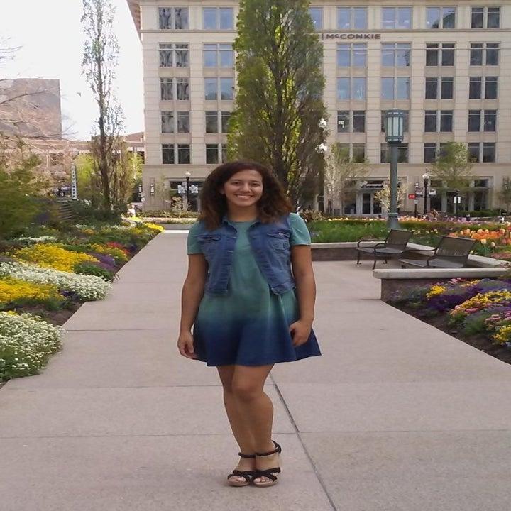 A reviewer wearing the dress under a denim vest