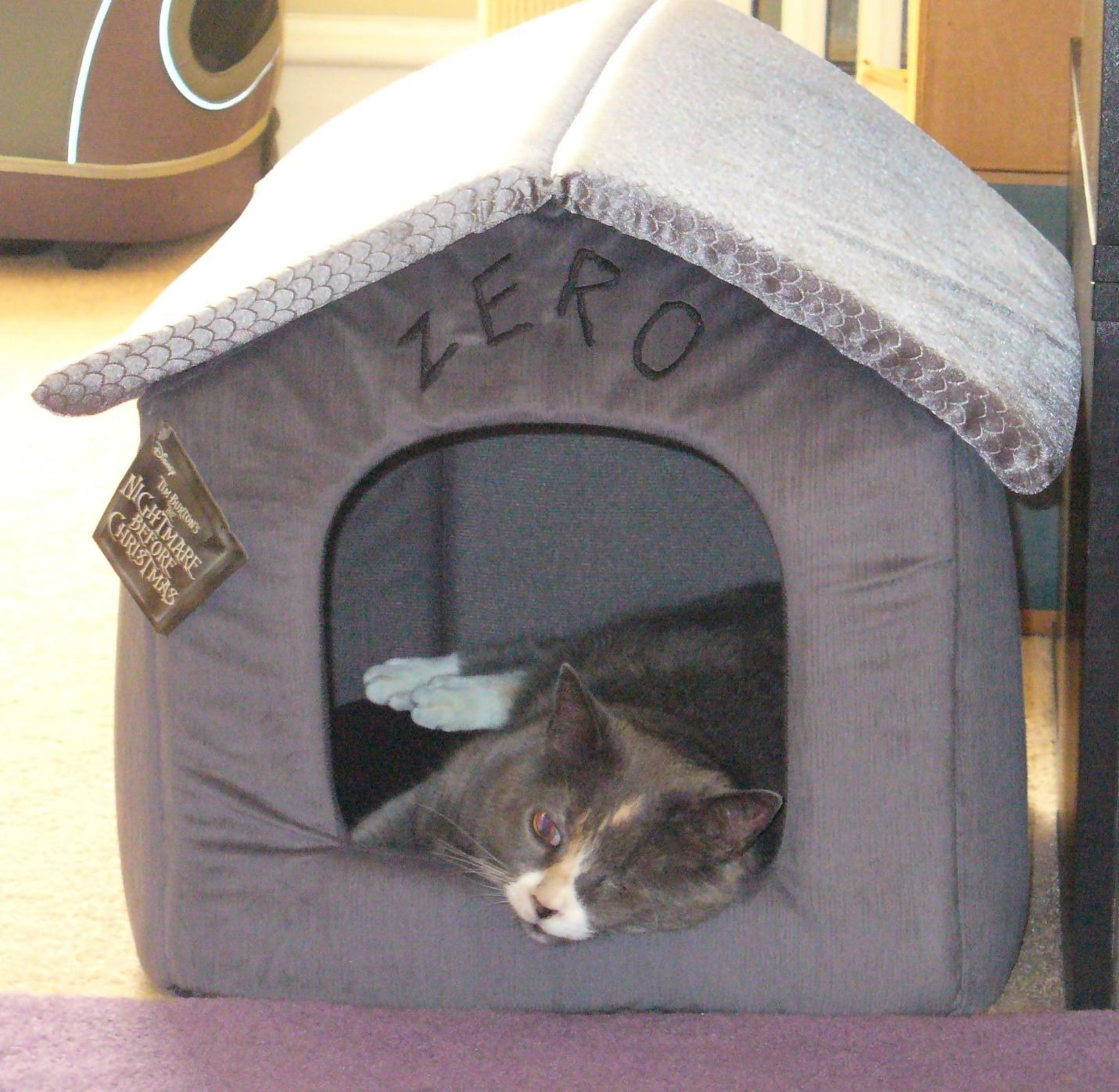 The small pet house/ bed, which has a rounded opening, grey body, and soft, removable roof
