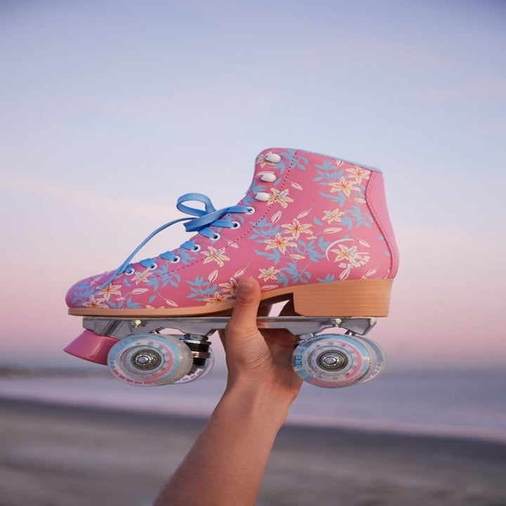 A hand holding a skate in the pink and blue wonderland print