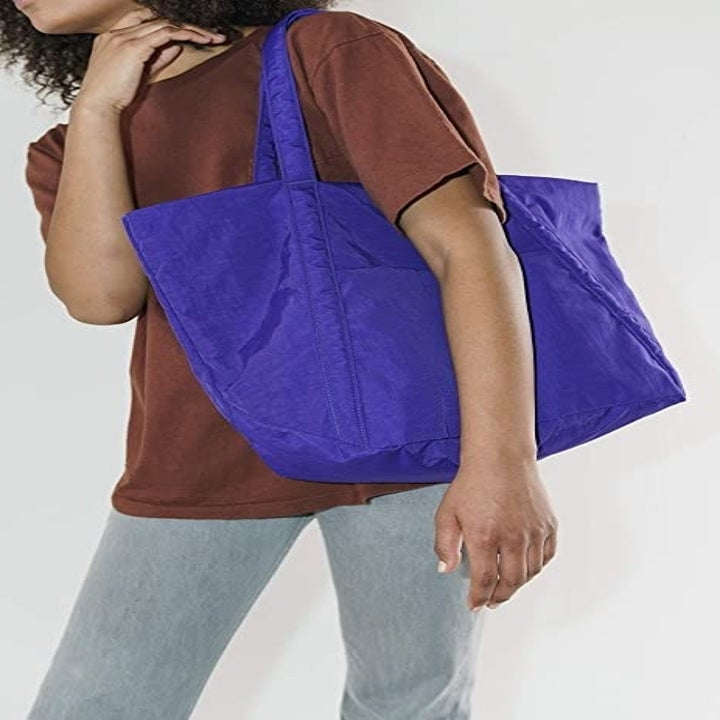Model wearing a large tote bag on their shoulder