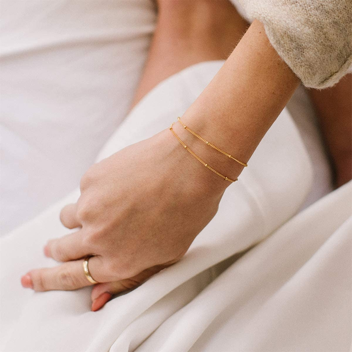 Model wearing layered gold bracelet