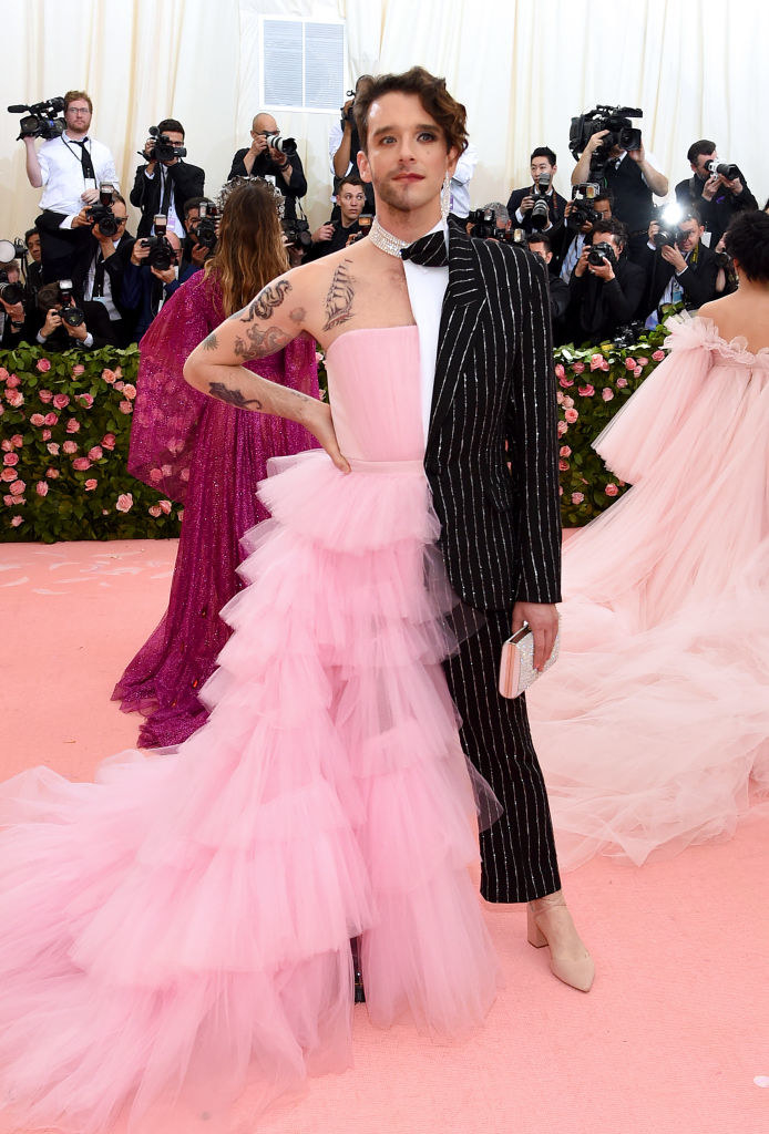 Michael in an outfit that's half a ballgown with ruffled tulle and a strapless top, and half a suit with glittered pinstripes and cropped pants with a nude heel