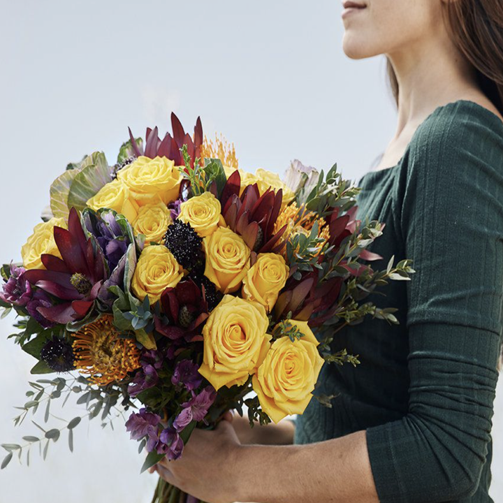 A model holding a bouquet of multicolor roses and other flowers