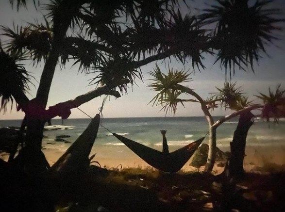A hand extended from a hammock at the beach