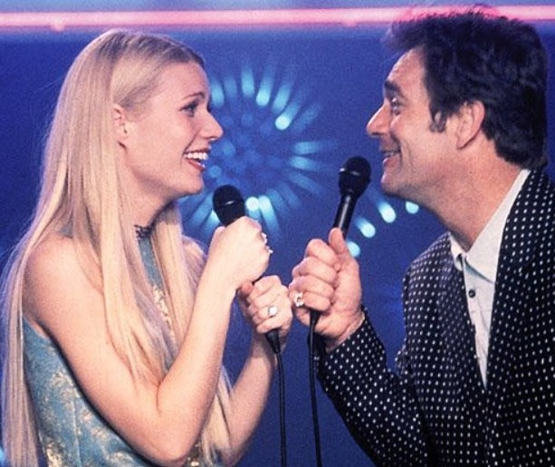Gwyenth Paltrow and Huey Lewis face each other holding microphones