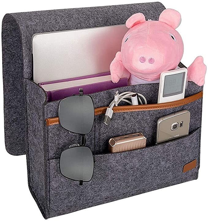 A tab, notebook, toy, cable, remote, cable, phone, and a pair of sunglasses kept in the caddy