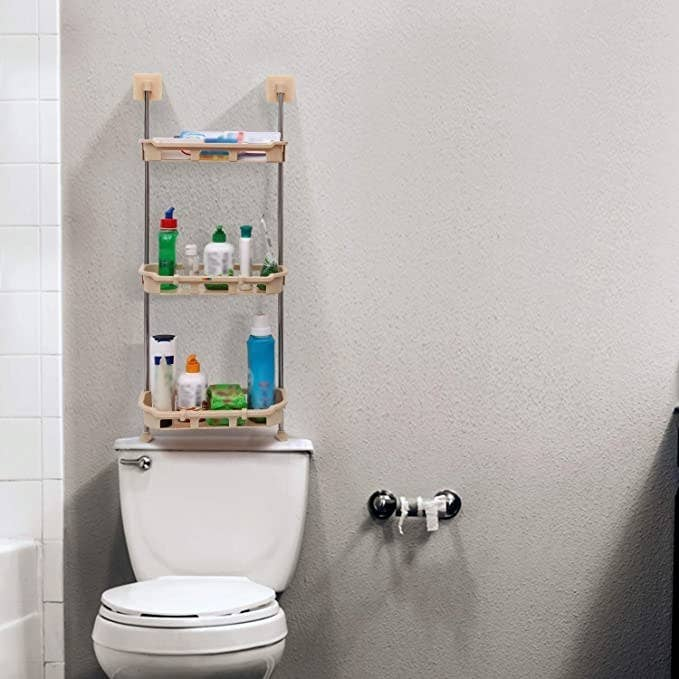 The rack is installed above a toilet. It houses toiletries and other bathroom products.