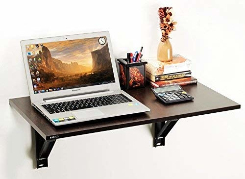 Wooden wall table with laptop and books on it.