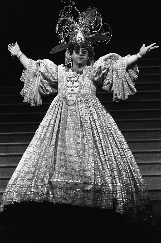 Elton in a large elaborate dress with trailing ruffled sleeves and a poofy skirt and large hat with swirling wire sticking out