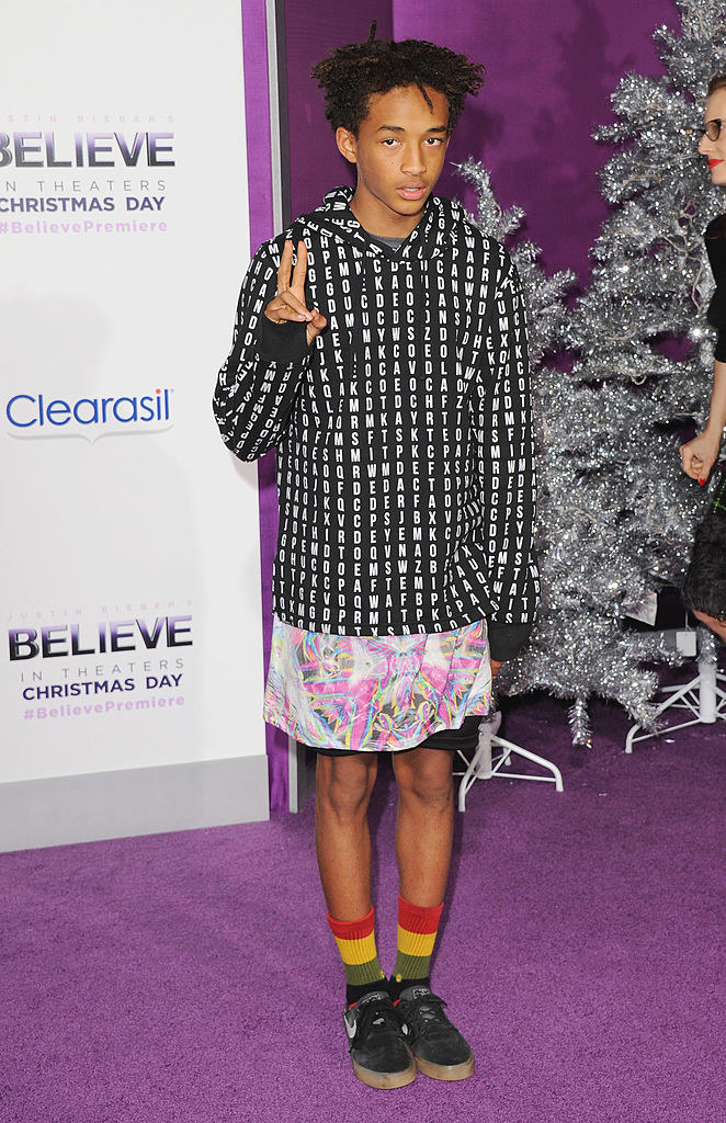 Jaden in a hoodie and loose patterned skirt underneath with long socks and sneakers