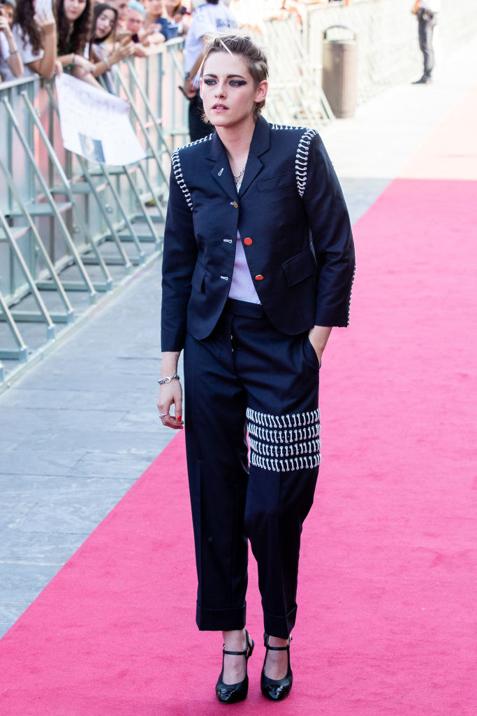 Kristen in loose cropped ankle pants with four layers of hanging chains mid-thigh on one leg and a loose jacket with only the top button fastened with similar chains around the shoulders