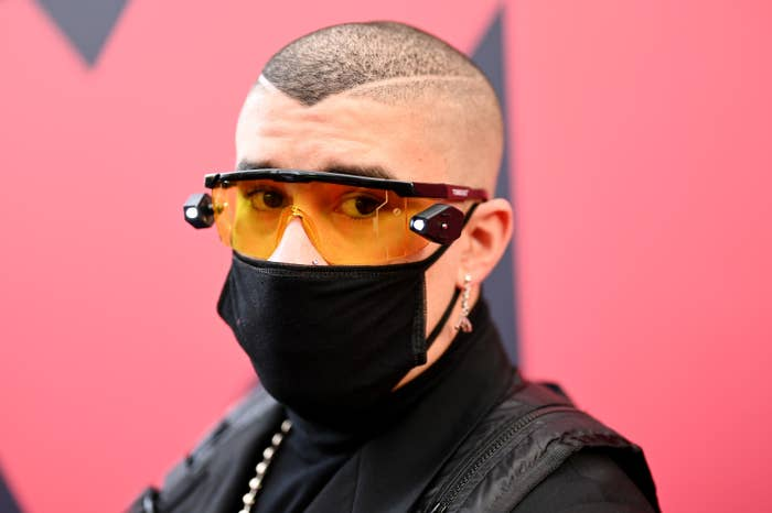 Bad Bunny posing on a red carpet wearing glasses and a face mask