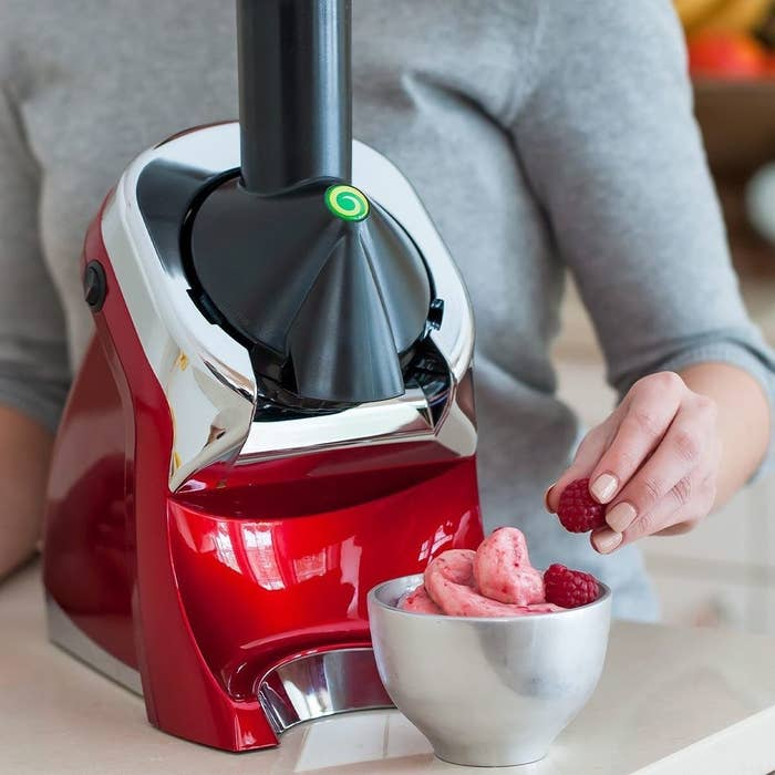 A person making raspberry ice cream with the Yonanas machine