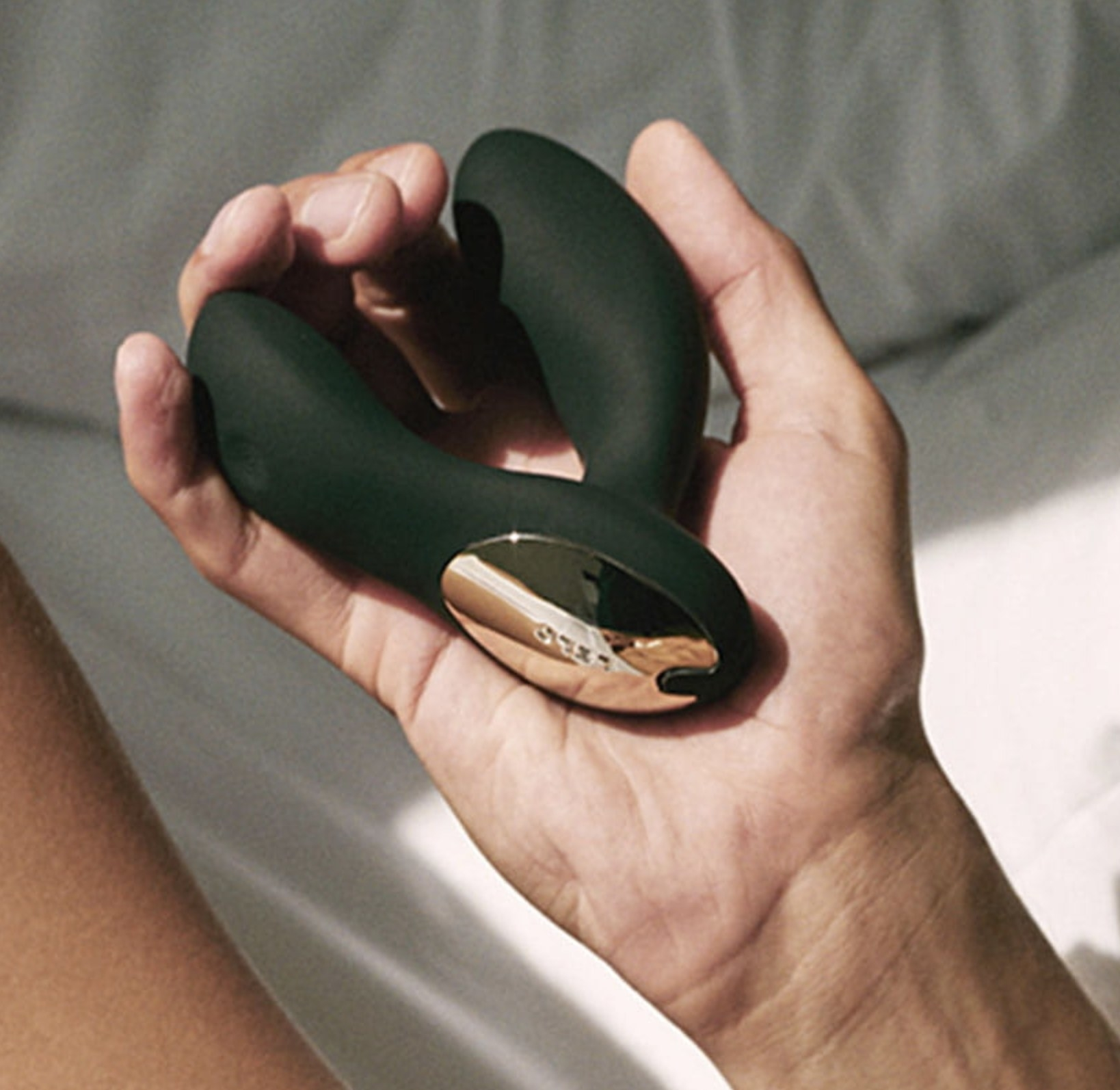 Person is holding a black prostate massager